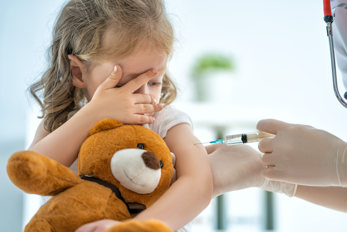child with teddy being vaccinated