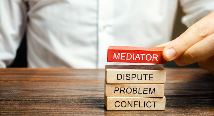 A man holds wooden blocks with the word Mediator, dispute, problem, conflict. Settlement of disputes by mediator. Dispute Resolution and Mediation. Third party, intermediary.